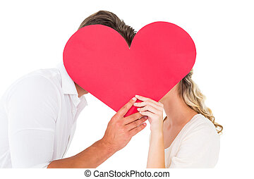 Attractive young couple kissing behind large heart