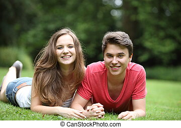 Attractive young couple lying on the grass