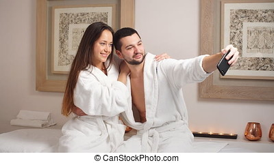 Attractive young couple makes a selfie in Spa Center.