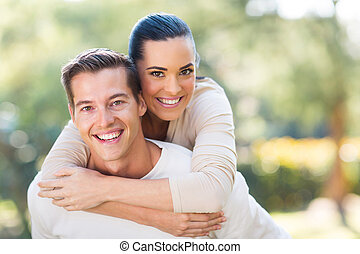 attractive young couple piggybacking outdoors