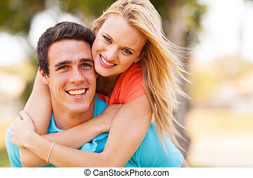 young couple piggybacking outdoors