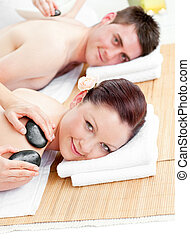 Attractive young couple receiving a back massage with hot...