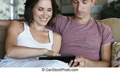 Attractive young couple relaxing together at home with a computer tablet.