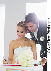 Attractive young couple signing wedding contract