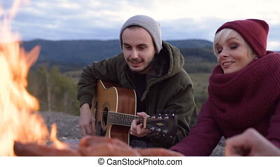 Attractive young couple sitting near fire and playing on the guitar on the mountain backgrounds.