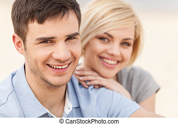 Attractive young couple sitting on beach at summer. happy couple sitting by beach and smiling
