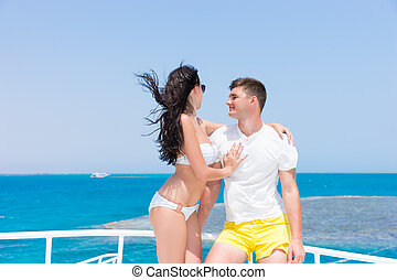Attractive young couple standing on the yacht at a sunny...