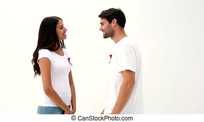 Attractive young couple supporting aids awareness on white...