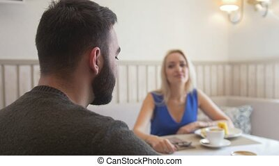 Attractive young couple talking while enjoying a cup of coffee at the cafe