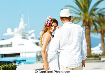 Attractive young couple walking alongside the marina in summer sunshine - wedding concept