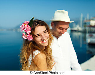 Attractive young couple walking alongside the marina - wedding concept