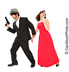 Attractive young couple with gun running in fear with clipping path.
