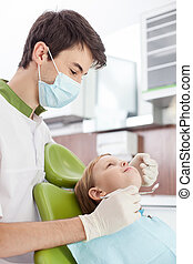 Attractive young dentist is treating small child