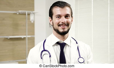 Attractive young doctor portrait in a hospital room looking...
