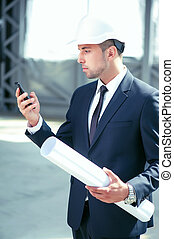 Attractive young engineer is using telephone for work
