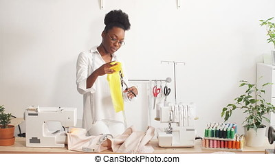 Attractive young fashion designer woman working at home studio.