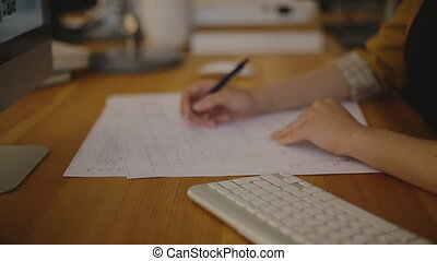 Attractive young female architect working at desk with plans on blueprint
