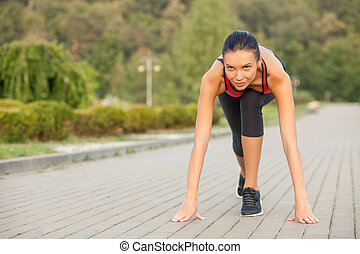 Attractive young female athlete is ready for running