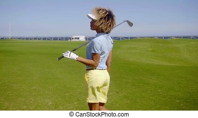 Attractive young female golfer watching the ball -...