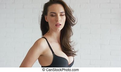 Side view of attractive young female in black bra touching hair and looking at camera while standing on white background