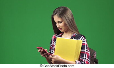 Attractive young female student using her smart phone smiling to the camera