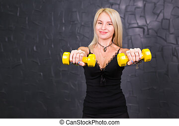 Attractive young fitness woman holding dumbell.