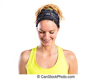Attractive young fitness woman in yellow tank top. Studio...