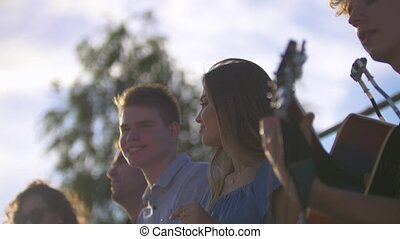 Attractive young friends hipsters singing songs with a guitar at summer sunset outdoors