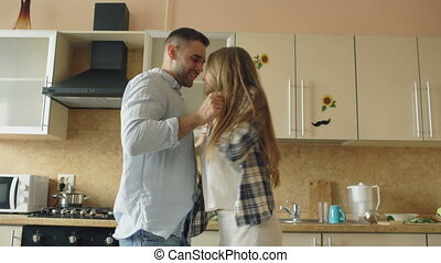 Attractive young funny couple have fun dancing while cooking...