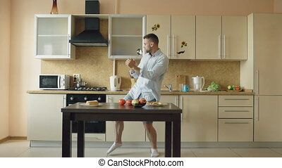 Attractive young funny man dancing and singing with ladle while while cooking in the kitchen at home