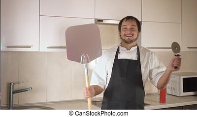 Attractive young funny man dancing while cooking in the kitchen at home