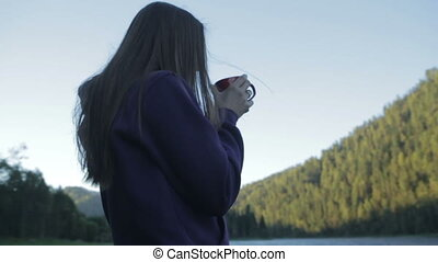 Attractive young girl drinking coffee from a cup