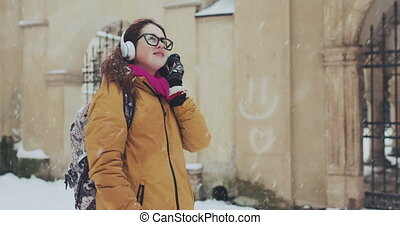 Attractive young girl Going the city and listening to music on the phone