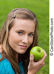 Attractive young girl holding a green apple while standing upright in the countryside
