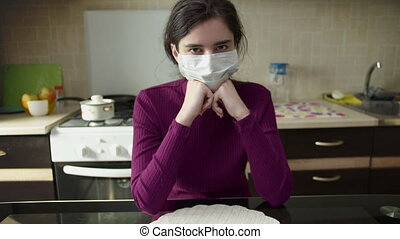 Attractive young girl in a medical mask sits at home, on the background of the kitchen