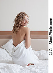 Attractive young girl in towel posing on bed