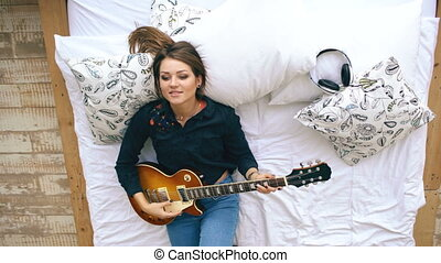 Attractive young girl learning to play electric guitar lie on bed in bedroom at home indoors