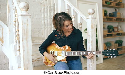 Attractive young girl learning to play electric guitar sit on stairs in bedroom at home