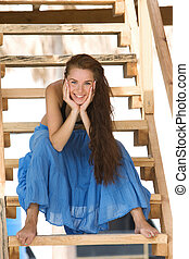attractive young girl sitting on wooden stairs