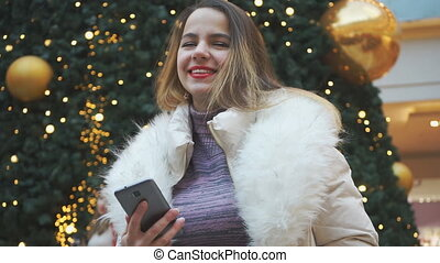 Attractive young girl smiling and then looking into the phone