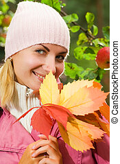 Attractive young girl with a bunch of autumn leaves
