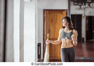 Attractive young girl with a green apple