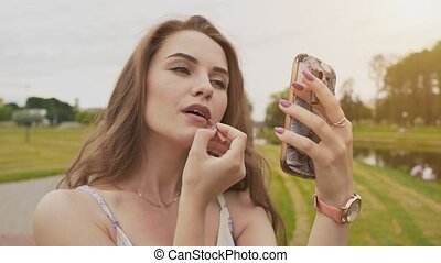 Attractive young girl with a smile on her face in a summer dress in a park colors her lips looking at the screen of a mobile phone. The youth. Summer. Beauty. Sensuality.