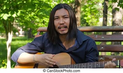 Attractive young guitarist singing in SLOW motion. Guitar player singing with passion and sitting on the bench in the park