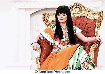 attractive young Gypsy woman sitting in a chair