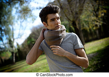 Attractive young handsome man, model of fashion in the park