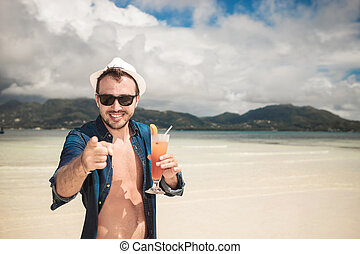 Attractive young happy man pointing at you