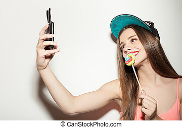 Attractive young hipster girl is photographing herself