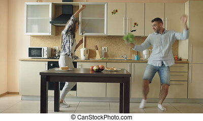Attractive young joyful couple have fun dancing and singing while cooking in the kitchen at home