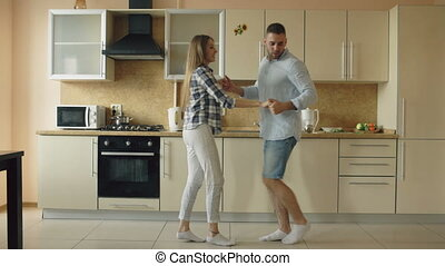 Attractive young joyful couple have fun dancing while...